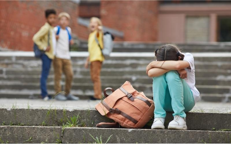 Criança a sofrer bullying de colegas no recreio da escola