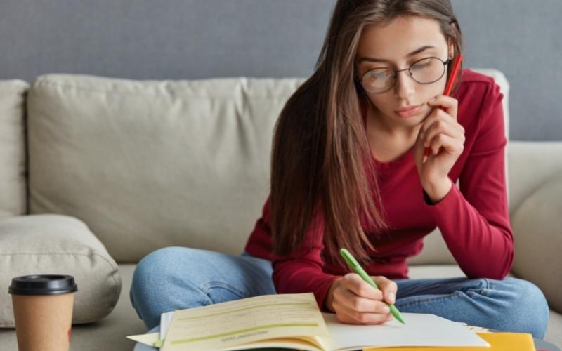 Rapariga jovem a planear estratégia para arranjar emprego e fazer o currículo