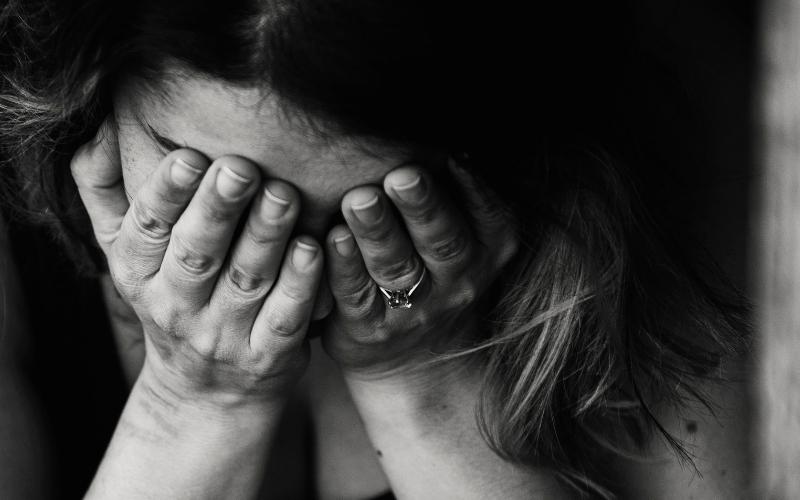 Mulher cabisbaixa, com as mãos na cara, triste ou em luto migratório